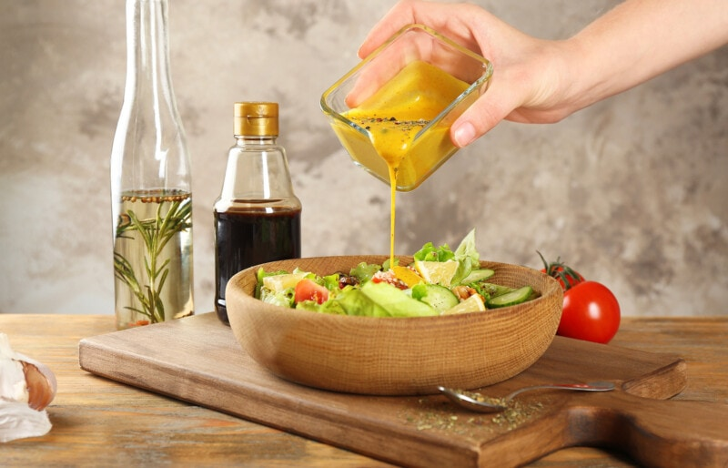 pouring honey mustard salad dressing from a container onto a salad