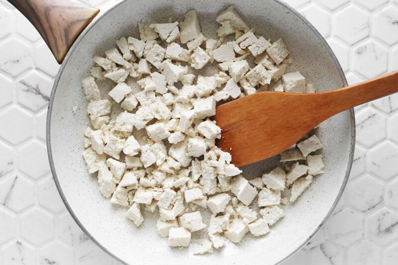 Cooking tofu in a skillet and stirring with a wooden spatula