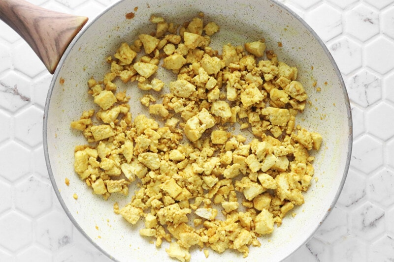 Tofu with spices added in a skillet look like scrambled eggs