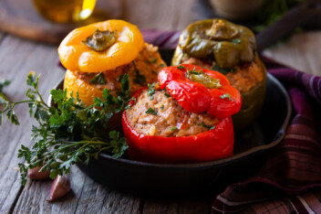 Stuffed bell peppers in a cast iron pan on a wooden table