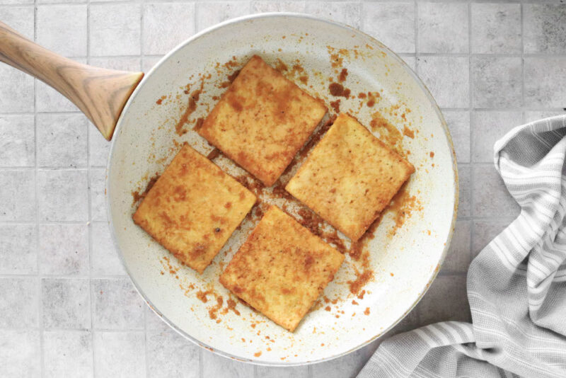 Frying coated tofu slices in a pan until crispy.