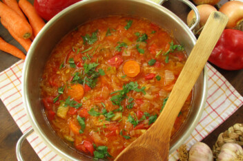 Cabbage soup in large pot with ladle, carrots, onion, pepper and garlic on the kitchen towel