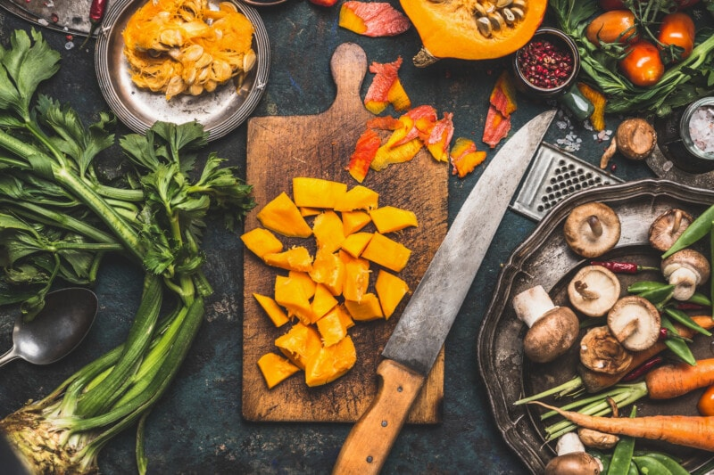 Chopped Pumpkin on rustic cutting board with kitchen knife and mushrooms and vegetables ingredients for tasty vegetarian cooking, dark styled, top view