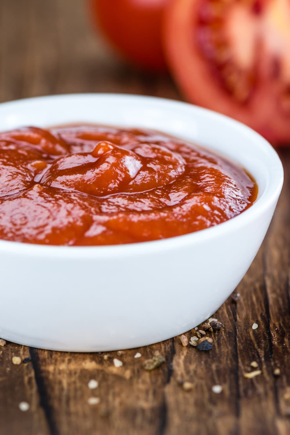 Vegan ketchup in a white bowl on a wooden table
