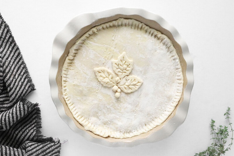 puff pastry dough on top of a vegan pot pie with leaf-shaped cut outs