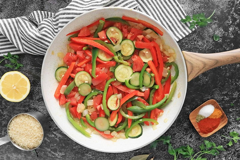 Garlic and tomatoes added to peppers, onions and zucchini in a skillet.