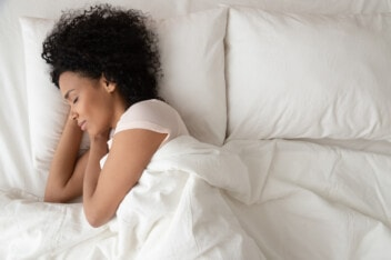 African American woman sleeping on white sheets