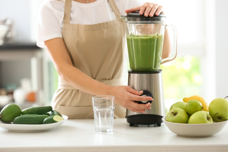 woman in tan apron using a blender to make a green smoothie